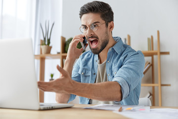 Annoyed male manager being dissatisfied with amount of financing, shouts as has phone conversation, sits in front of opened laptop expresses irritation. Enterpreneur discontent with market fluctuation