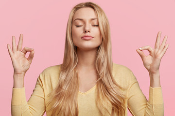 Blonde beauiful young female makes mudra sign, relaxes after hard working day, keeps eyes shut, practises yoga against pink background. Young pretty woman meditates indoor. Relaxation concept