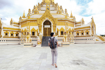 Back of young man backpacker walking towards Burmese temple named Buddha  Relic Tooth Pagoda in Yangon, Myanmar.
