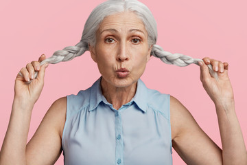 Mature playful female rounds lips, shows her two grey pigtails, has funny expression, dressed in blue blouse, isolated over pink studio background. Elderly beautiful woman has fun alone indoor.