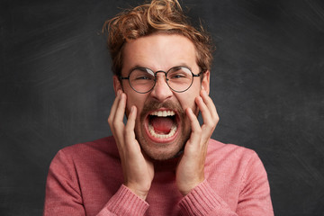Fierce mad young male shouts and exclaims in anger, keeps mouth widely opened, looks desperately at camera, isolated over black background. People, problems, anger and negative emotions concept