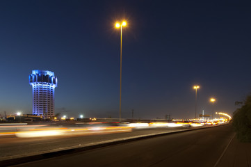 Jeddah water tower at night, with car lights motion on the street. Fotomurales