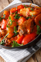 Slow cooked beef with potatoes, tomatoes, pepper, carrots and onions close up in a bowl. vertical