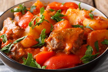 Filipino beef stew mechado with potatoes, peppers, carrots and onions close up in a bowl. horizontal