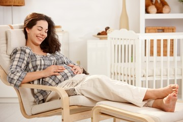 Pregnant woman resting in armchair in nursery