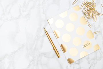 Notebook and stationery items of gold color. Feminine desktop.