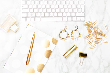 Keyboard and of office items of gold color and cosmetics on the desktop. Flat lay
