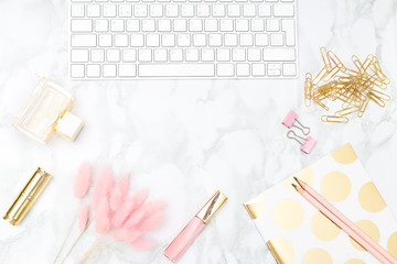 Blush and gold feminine desktop with makeup and keybord. Copy space