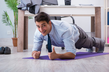 Businessman doing sports in office during break
