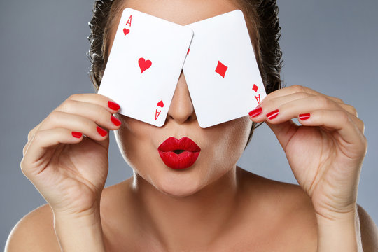 Woman with red lips is holding two aces in her hands