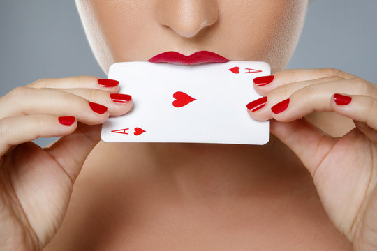 Woman with red lips is holding ace card in her hands