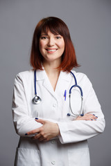 Image of smiling female doctor in white coat and with phonendoscope