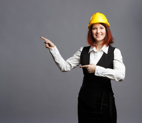 Photo of brunette builder in yellow helmet pointing finger at empty space