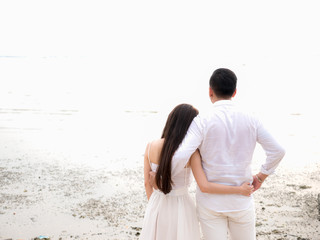 Young Asian couple in love on the beach.