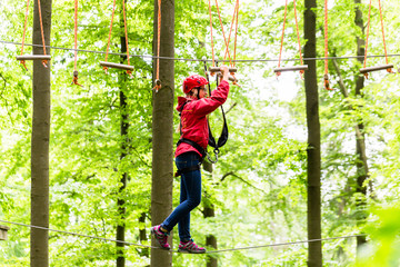 Child reaching platform climbing in high rope course in forest