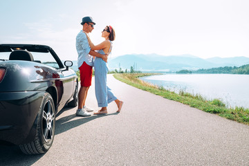 Couple in love stands near the cabriolet car on the picturesque mountain road