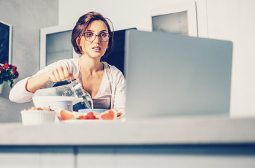 Woman prepare breakfast and watch laptop on kitchen.