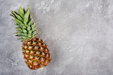 Fresh ripe whole pineapple on gray concrete background