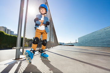 Young inline skater standing at outdoor rollerdrom