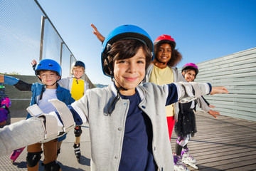 Preteen boy rollerblading with friends outdoors