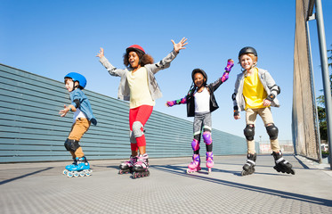 Joyful kids rollerblading outdoors at sunny day
