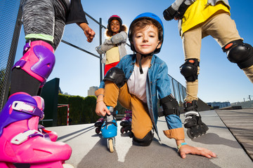 Cute boy in safety gear on roller skates outdoors