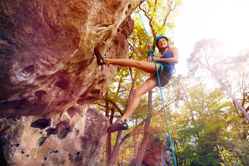 Young woman in helmet rock climbing at sunny day