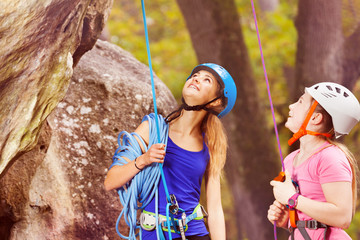 Rock climbing trainer with teenage girl looking up