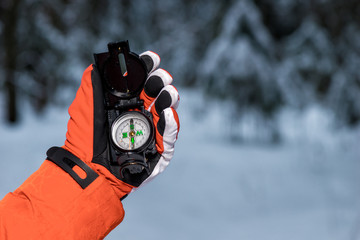 hand with a compass in the frost on a snowy forest background