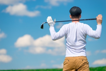 Golfer in a field with a golf club on his shoulders resting after a successful game