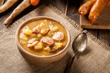 Wooden bowl of split pea soup with sausage and potatoes