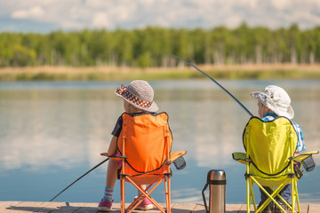 Wall Murals Fishing children with fishing rods sit on a wooden pier and fish at the lake