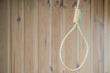empty noose of the rope on the background of wooden wall close-up