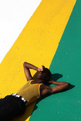 Man napping on the ground painted in multiple colors