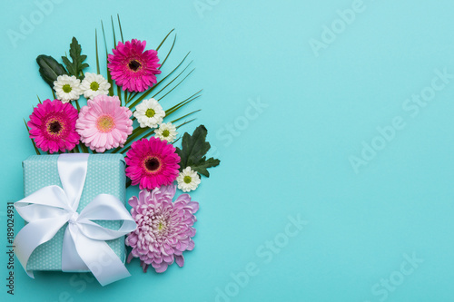 Happy Mother's Day, Women's Day, Valentine's Day or Birthday Pastel Candy Colors Background. Floral flat lay greeting card with beautifully wrapped present and copy space.