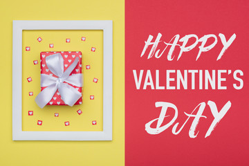 Happy Valentine's Day Pastel Candy Colors Background. Valentines day flat lay minimal concept with beautifully wrapped present and loads of tiny hearts.