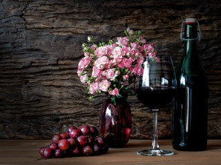 Still life visual art of grapes, a glass of wine, a bottle of wine and pink roses in a red vase on wooden slab with wooden back drop