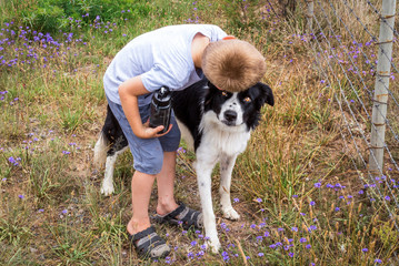 Boy hugging Border Collie pet dog outdoors on farm