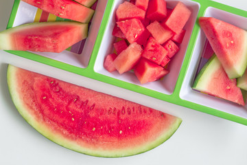 Watermelon cuts and slices in serving platter on white background - Top view photo