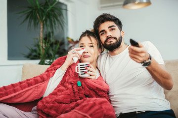 Couple in love hugging and enjoying favorite tv show together.