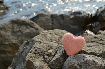 Pink bath salt figure in a heart shape on a sea rock with a sea water behind