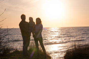 family at sunset by the sea