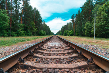 Photo sur Plexiglas Voies ferrées Rusty railroad with rocks in the forest under light blue cloudy sky. Old railroad in poor country.
