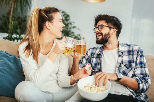 Couple in love enjoying their free time, sitting on a couch,drinking beer and eating popcorn