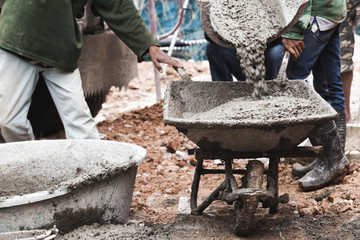 industrial construction labor work concrete mix with cart
