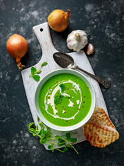 Green sweet pea and mint soup with cream and olive oil drizzle served with grilled ciabatta toasts
