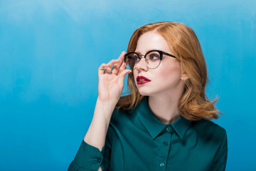 A woman demonstrates a new pair of glasses, looking to the side on a blue background