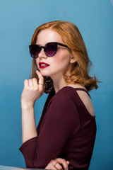 Redhead sexy beautiful girl with makeup and red lips in sunglasses on blue background.
