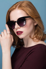 Close up portrait of stylish young woman in sunglasses against blue background. Fashion, glamour, fashion, model