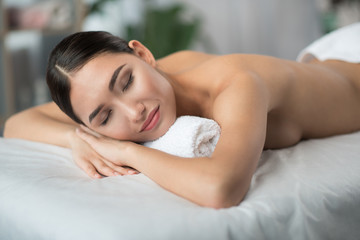 Portrait of satisfied young asian woman lying on massage table at spa. Her eyes are closed with relaxation